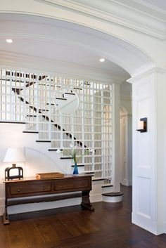 Interesting staircase; love the console table; paneling; stained floors w/different pattern at threshold