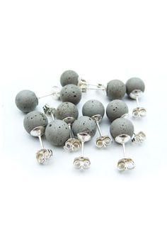 $60 These cement earrings are modeled on classic pearl studs. Each concrete sphere is cast by hand and set onto a sterling silver post. With wear, the colour of the earrings will deepen as the concrete is exposed to the air and the oils from your skin.