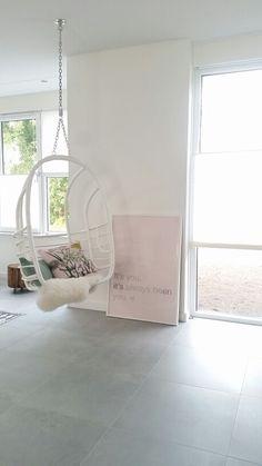 Scandinavisch wonen. Wit wonen gecombineerd met zachte pasteltinten. Hangstoel van Moodadventures. Tegelvloer Loft Silver van VT Wonen