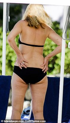 Jerry Hall wows in skimpy black bikini as she enjoys beach stroll White Swim Shorts, London In March, Jerry Hall, Halterneck Bikini, Black Two Piece, Star Wars, White Caps, Ageless Beauty, Loose Tops