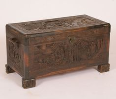 Chinese carved, footed camphor chest; deep scenic carving on all sides, foliate handles, interior tray.