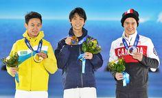 ソチ五輪男子フィギュアスケートで優勝し、銀メダルのパトリック・チャン(右、カナダ)、銅メダルのデニス・テン(左、カザフスタン)とともに表彰台でポーズを取る羽生結弦(2014年02月15日) 【AFP=時事】