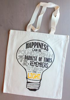 Happiness can be found even in the darkest of times if one only remembers to turn on the light. tote bag