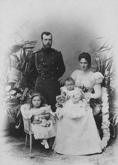 Nicolau II, Imperador da Rússia, Alexandra Feodorovna, imperatriz da Rússia e grã-duquesas Olga Nikolaevna e Tatiana Nikolaevna. Nicolau II está em pé à esquerda, vestindo uniforme militar. Alexandra Feodorovna está sentada ao lado dele para a direita segurando a bebê grã-duquesa Tatiana em seu joelho. Grã-duquesa Olga está sentada em uma pequena cadeira na frente de seu pai, segurando uma boneca. Há plantas ao seu redor. Em 1898.