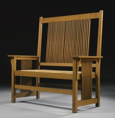 Gustav Stickley,  TALL-BACK SPINDLE SETTLE, MODEL NO. 286, with firm's decal, oak with the original rush seat, circa 1905, executed by the Craftsman Workshops of Gustav Stickley, Eastwood, NY.
