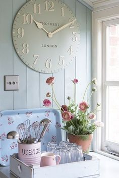 Kitchen with pale blue wainscoting  white trim. Love the oversized wall clock  sweet blue touches .