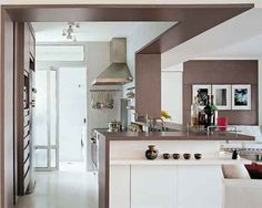 Os arquitetos Alice Martins e Flávio Butti integraram a cozinha e o estar. A finalização ficou por conta da faixa de madeira, que se movimenta do chão ao teto e percorre a bancada. Via Casa.com