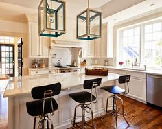 Amazing kitchen features tray ceiling accented with Urban Electric Company Cosy Lights illuminating marble top island lined with vintage architect's barstools situated across from ivory paneled hood over high-end, stainless steel stove.