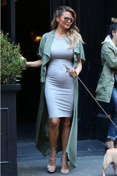 Taking pregnancy style cues from Kim Kardashian's maternity uniform, Teigen steps out in a form-fitting gray knit dress layered underneath a floor-length olive jacket. - HarpersBAZAAR.com