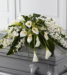 Sympathy Flowers - FTD Angel Wings Casket service. White Dendrobium orchids, white calla lilies, green hydrangea and a variety of lush greens are artfully arranged to perfectly adorn the top of their casket, offering the colors and ambience of grace and serenity. Approximately 36W x 22D.