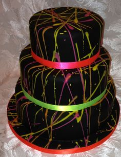 3 tier, chocolate fudge cake, black fondant with neon icing and ribbon. Also has a layer of smarties in the centre!