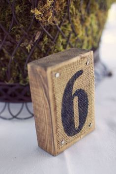 Rustic Wedding Table Numbers. Printed burlap nailed to a piece of wood. Cute!