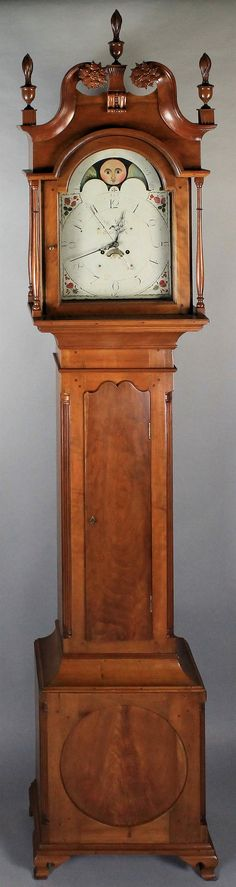 """CHIPPENDALE CARVED CHERRYWOOD AND FIGURAL MAHOGANY TALL CASE CLOCK, GEORGE WOLTZ, HAGERSTOWN, MARYLAND ca. 1800, the hood with swan's neck molded crest ending in carved rosettes and centering three urn and stylized flame finials, above an arched hinged glazed door opening to a white-paint dial with phases of the moon, calendar date register, and the inscription """"George Woltz, Hagerstown,"""" turned colonnettes flanking; the waisted case with shaped hinged door flanked by fluted ..."""