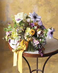 This arrangement is brimming with purple, green, and yellow flowers, but the muted tones make it more