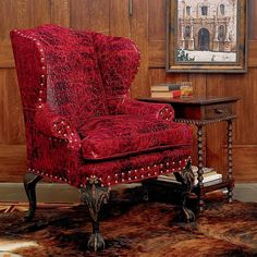 """As comfortable as it is eye-catching, this Red Gator Chair lends a brilliant splash of color to any dšcor. The bayou ôgatorö pressed cowhide leather upholstery gives it an authentic antique look while the eight-step English black walnut finish and hand-applied, antiqued goldtone nailheads make each piece truly unique. 40""""w x 34""""d x 49""""h. Made in USA. Please allow 12-14 weeks for delivery. Note: Due to differences in dye lots, climate, the uniqueness of the artisan's application, ..."""