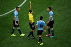 Diego Godin of Uruguay is shown a yellow card by referee Carlos Velasco Carballo during the 2014 FIFA World Cup Brazil Group D match between...