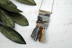 This one-of-a-kind weaving was handmade using a variety of natural and recycled fibers, making it an absolutely unique piece of art. Each woven pendant is attached to sturdy necklace hardware and includes a 28 chain. Weavings are 1.5 wide and range from 3-5 in length (including tassels). Please handle weavings delicately and avoid getting them wet. If you prefer to hang your teensy weaving in a dollhouse, or display it in another way, I can alter the length of the chain for you! Just leave…