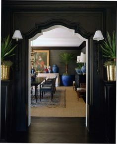 Dark walls, carved doorway, sconces, brass accents - looking into a dining room with grasscloth, old rug over sisal and blue accents - Mary McDonald