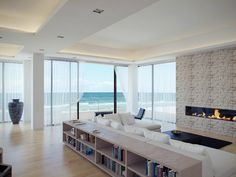 Living Room: Wooden Book Storage And Stone Fireplace With Clean Sofa: Beautiful and Minimalist Living Room Design with Panoramic View