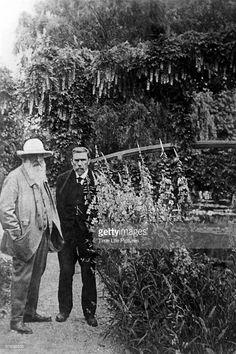 French painter Claude Monet (1840-1926) & Gustave Geffroy walking in Monet's garden.
