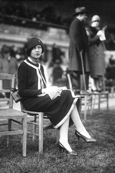 A women sits comfortably in 1925 fashions: a jumper suit with contrasting trim, worn with a cloche hat with turned back brim.