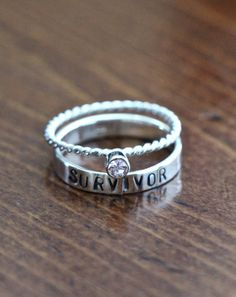 "Give someone you care about a sterling silver survivor stackable ring set to commemorate her courageous victory over one of life's most severe challenges. The ""Survivor"" ring is hand stamped and stacked with your choice of Swarovski crystal ring to represent the color of your special cause. Order a cancer survivor jewelry gift to bring awareness and celebrate life at the same time!"