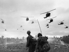 The second wave of combat helicopters of the 1st Air Cavalry Division fly over an RTO and his commander on an isolated landing zone during Operation Pershing, a search and destroy mission on the Bong Son Plain and An Lao Valley of South Vietnam, during the Vietnam War. The two American soldiers are waiting for the second wave to come in. (Photo by Patrick Christain/Getty Images)