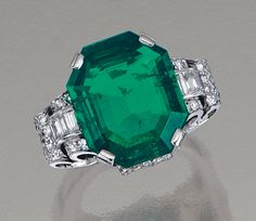 EMERALD AND DIAMOND RING, CIRCA 1935.  Centring on an octagonal step-cut emerald weighing 7.77 carats, embellished by stylised scrolls elements set with single-cut and baguette diamonds,