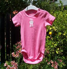 Pink short sleeved organic cotton bodysuit with bunny applique.  Ready to ship in size 9-12 M. $16.19