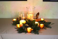 Candle centerpiece inspiration: Trio of pillar candles in cylinder vases with silver dollar eucalyptus tucked around