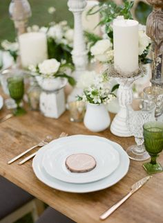 Pretty table: mismatched white vases, white candles, and flower posies