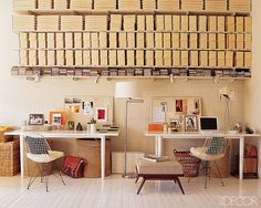 Identical workstations are set up along a brick wall in photographers Laura Resen and Cloud Devine's New York City loft, which they designed with Thomas O'Brien. Shelving holds boxes filled with art and film supplies, the Eames chairs are vintage, and the floor is coated in Benjamin Moore industrial paint.