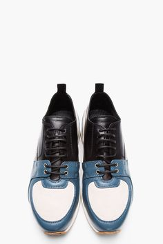 KRISVANASSCHE // Blue Leather & Suede Derby-Sneaker Hybrids 32134M050003 Low top leather shoes in blue. Round toe. Derby style upper with black lace up closure and silver tone eyelets. Sneaker style toe with suede panel and rubber detail. Paneled upper in grey suede and blue leather. Pull loop at heel collar. Off-white rubber foxing. Tonal stitching. Leather upper, rubber sole. Made in Italy. $965 CAD