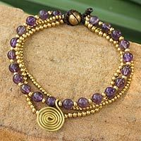 Amethyst beaded wristband, 'Daydreams'. A gleaming spiral charm evokes daydreams, while jingling bells form the clasp.