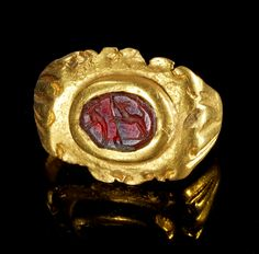 Golden ring with a gemstone made of garnet depicting two jumping dogs. Roman, 2nd - 3rd century A.D.