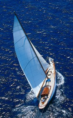 don't know what kind of boat this is, but the light blue hull & sails are beautiful