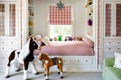 Sweet girl's room features a built-in reading nook bed with drawers dressed in red gingham bedding ...