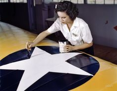 "August 1942. Corpus Christi, Texas. ""Women from all fields have joined the production army. Miss Grace Weaver, a civil service worker at the Naval Air Base and a schoolteacher before the war, is doing her part for victory along with her brother, who is a flying instructor in the Army. Miss Weaver paints the American insignia on repaired Navy plane wings."""