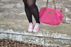 Detail of pink Converse All Stars shoes with black tights and pink hand bag