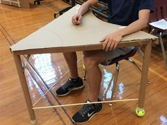 Chest down, a teen is sitting at a hand-made desk. It& made of a cardboard triangular desktop, three cardboard tubes as desk legs -- with tennis balls at the bottom of two of them -- and two solid, cylindrical wooden rods connecting the desk legs. Problem Based Learning, Stem Learning, Project Based Learning, Learning Spaces, Learning Environments, Growth Mindset Classroom, Sustainability Projects, Engineering Projects, Engineering Challenges