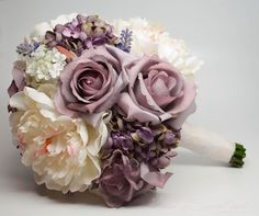 A shabby chic bouquet with lavender roses and hydrangea, as well as ivory peonies and lace. From the KateSaidYes shop on Etsy.
