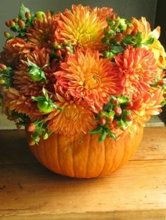 fall decorations : hollowed pumpin, florist foam, real flowers and berries= beautiful centerpiece