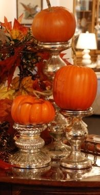 "From Nell Hill's Blog: ""This is one of my go-to looks for fall because it's obscenely easy to do, yet looks dramatic. Find a great candlestick, remove the candle, and replace it with a pumpkin or gourd. In the example above, we collected a trio of different sized pillar candlesticks made out of mercury glass, clustered them together and topped them with assorted pumpkins. For a slight variation of this look,... tiny fall wreath under them."""