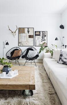 Cadeiras acapulpo pretas com almofadas estampadas, tapete felpudo, mesa de centro de madeira e obras de arte abstrata na sala de estar: