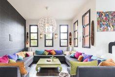 déco salon moderne - des coussins multicolores éparpillés sur les canapés gris, une table basse en vert pistache