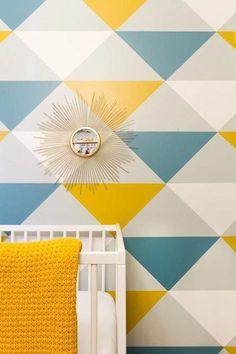 Papel pintado vintage con estapado de triangulos azul, amarillo gris y blanco. Papel pintado infantil