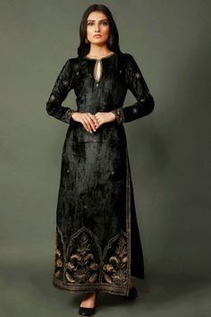 A truly gorgeous piece in luxurious black chenille. This long kurta features side slits and a keyhole neckline. It has been enhanced with golden zari embroidery in Mughal patterns for a royal finish. Dress Indian Style, Indian Fashion Dresses, Indian Designer Outfits, Designer Dresses, Fashion Outfits, Velvet Suit Design, Velvet Dress Designs, Velvet Kurtis Design, Fancy Dress Design