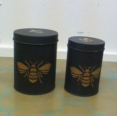 Set of two tin Canisters, large and medium size, painted in ASCP in graphite and stenciled in gold With the French bee and fluer-d-le design. Use in kitchen, bathroom, or just display. Call for shipping details.