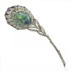 An Edwardian gemset peacock feather brooch, set with an oval cabochon-cut opal, estimated to weigh 3.35 carats, old-cut and rose-cut diamonds, triangular-shaped emeralds, and sapphires, circa 1900.