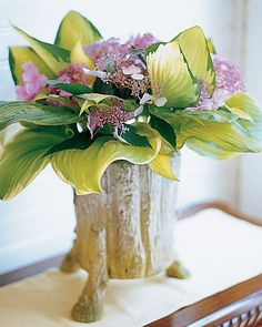 Fit an arrangement of lush hosta leaves and lavender hydrangeas into a tree trunk-inspired vase.
